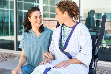 Nurse Looking At Patient Sitting On Wheelchair At Hospital