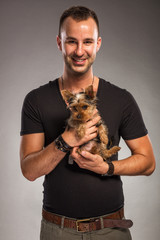 Handsome young man holding a yorkshire terrier dog