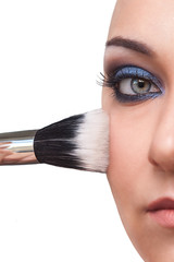 Detail of the face of a girl with a brush for makeup