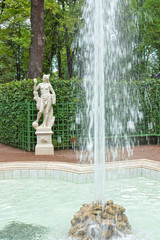 Square fountain and antique statue in the Summer Gardens park
