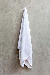 Hanging white towel draped on exposed concrete wall in the bathr