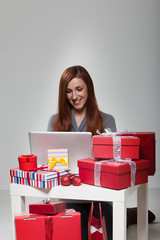 Gifts in Front Smiling Young Woman Using Laptop