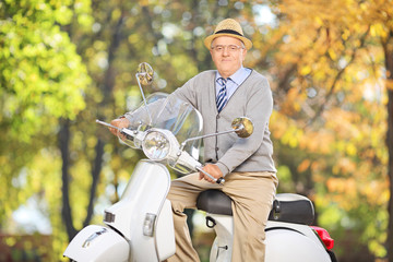 Senior gentleman posing on scooter in a park