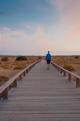 Man walking by a wooden footbridge. Dunes, Algarve, Portugal