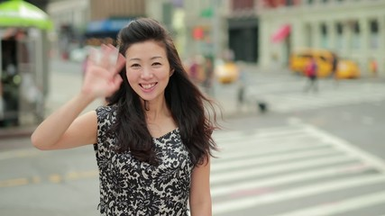 Young Asian woman in city waving hands smiling