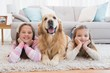 Sisters lying on rug with golden retriever smiling at camera - 70981380