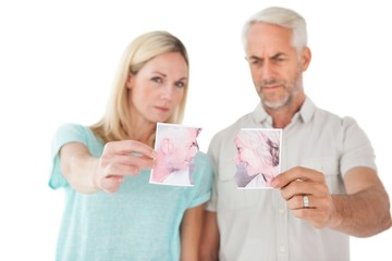 Couple holding two halves of torn photograph