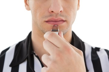 Mid section of referee blowing whistle