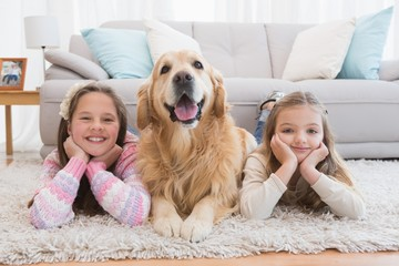 Sisters lying on rug with golden retriever smiling at camera