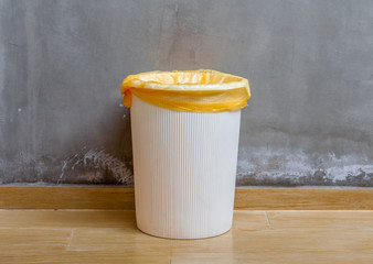 The white plastic bin with orange bag on wooden floor with expos