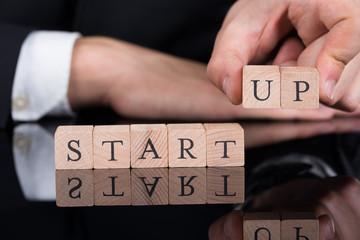 Businessman Arranging Startup Blocks On Desk