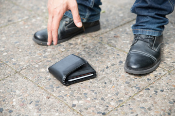 Man Picking Up Fallen Wallet