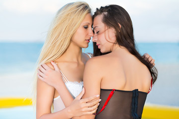 Two kissing women wearing sexy lingerie