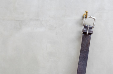 The black leather belt hanging on the hanger with exposed concre