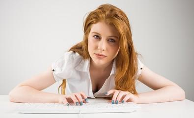 Pretty redhead typing on keyboard