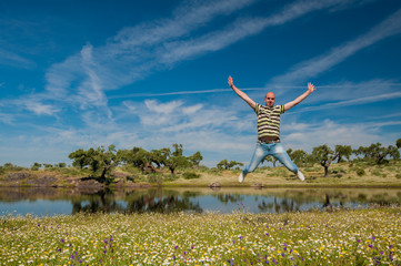 Man jumping in the pasture, pond and oaks. Extremadura