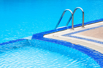 A view of curved light clear blue swimming pool with steel ladde