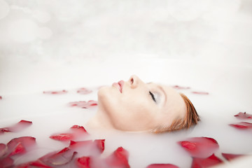 beautyfull redhead girl taking relaxing bath with flower petals