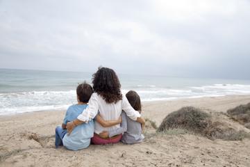 Madre contemplando el mar con sus hijos