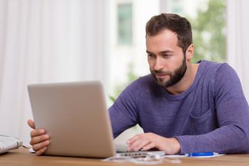 mann arbeitet zuhause am laptop