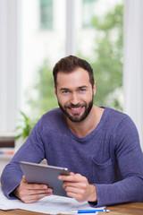 glücklicher mann mit bauplänen und tablet