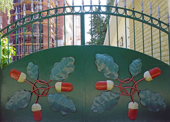Green metal gate with forged pattern in the form of acorns