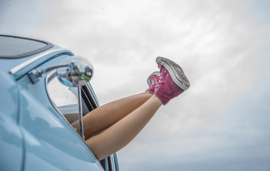 girl with legs outside her car