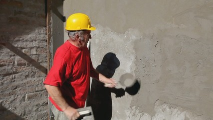 Worker spreading mortar with trowel to wall, construction site