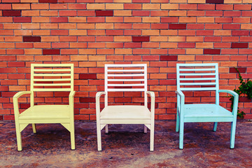 color wooden chair with brick wall