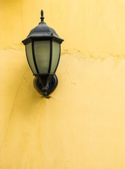 Vintage style lamp on rustic yellow wall