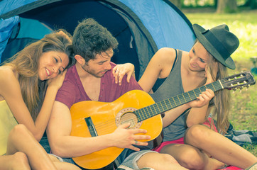 friends playing guitar on camping