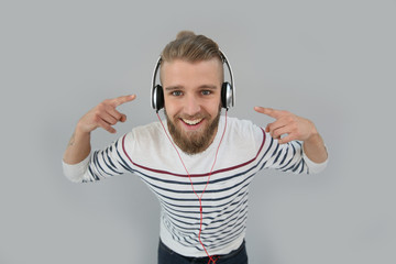 Cheerful trendy guy listening to music