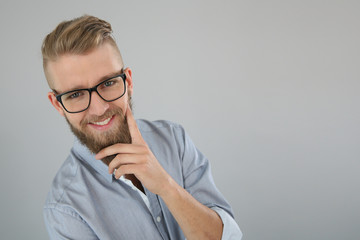 Trendy guy with hand on chin, isolated