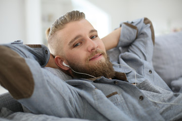 Young man relaxing in sofa, listening to music
