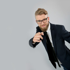 Trendy businessman pointing at camera, isolated