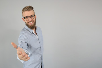 Smiling trendy guy giving hand for handshake