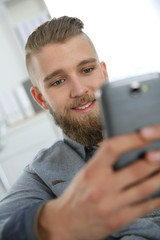 Young man sending text message with smartphone
