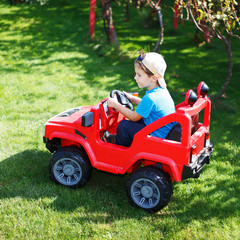 Little boy drive electrical vehicle in garden