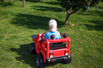 Little boy in cap drive electrical vehicle