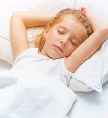 little girl sleeping in white bed