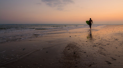 A single surfer on the shore, with the sun setting behind him