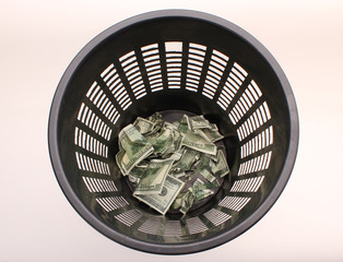 Money in basket. Dollars in the trash bin