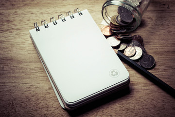 note pad, pencil and coins