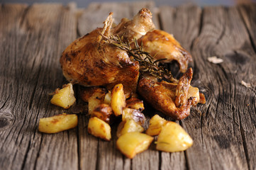 Baked chicken with potatoes on woooden table