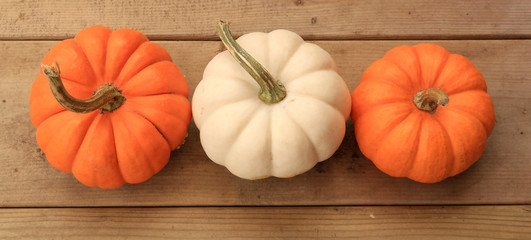 Three pumpkins on wood boards