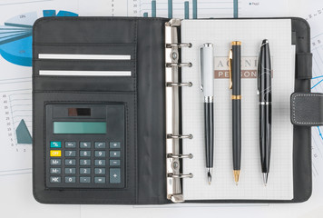Diary, calculator and three pen lying on a background of diagram