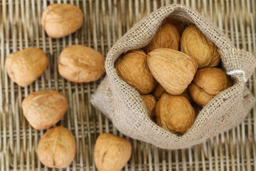 Whole walnuts in jute bag on wicker background, close up