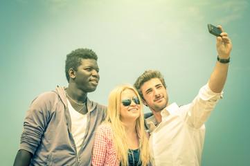 Group of multiracial happy best friends taking a vintage selfie