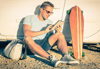 Young hipster man with tablet and car - Vintage travel concept