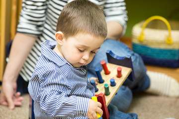 Little child boy playing in kindergarten in Montessori Class.